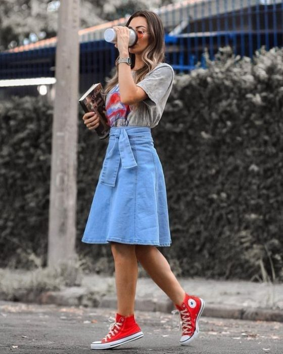 Blonde girl drinking coffee in denim midi skirt, red converse and gray blouse