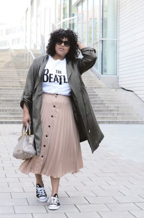 Plus size girl in pink midi skirt with white blouse and green jacket
