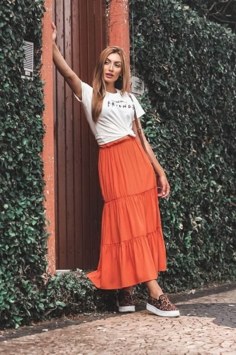 Tall slim girl in white blouse and orange midi blouse