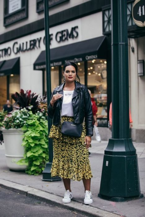 Brunette girl in leather jacket, white blouse and yellow midi skirt with black