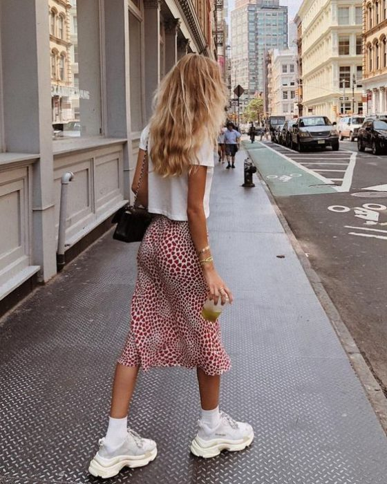 blonde girl in white blouse, red midi skirt and white low top sneakers