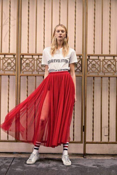 Chica llevando falda plizada en tono rojo con transparencias