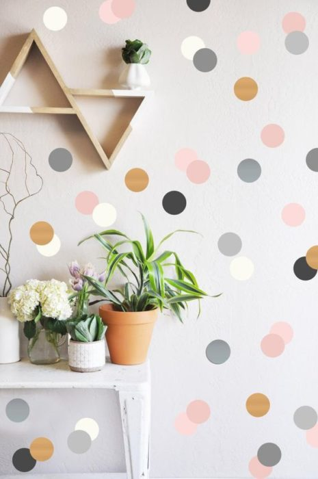 Decoración de pared con fondo gris y puntos rosas, negros, dorados y grises