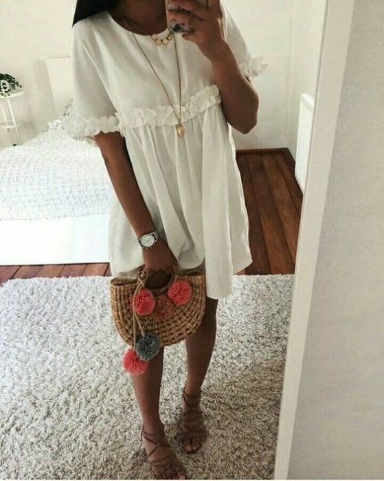 Woman takes selfie in front of mirror with white dress and basket bag