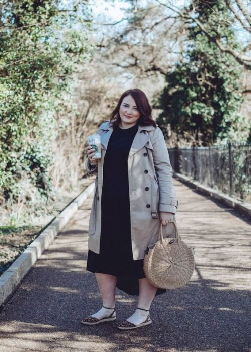 Plus size woman in beige trench coat and black dress with circular basket bag