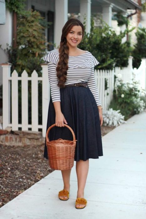 Woman in white striped blouse with azuk, long skirt and basket bag