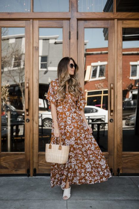 Mujer de cabello largo castaño con vestido de flores largo y bolsa tipo canasta