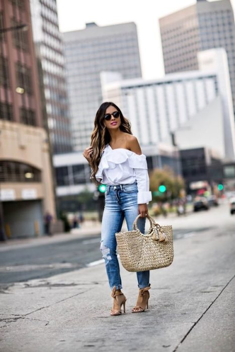 Woman in white shirt, jeans and triangular basket bag