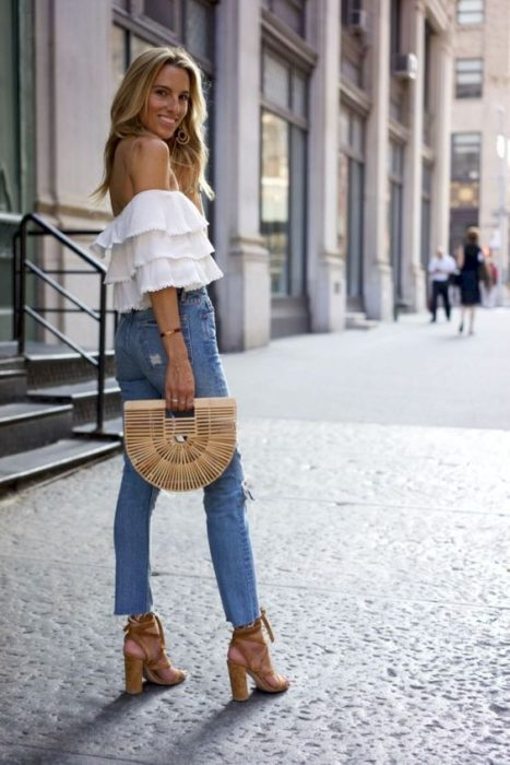 Girl posing on the street with jeans, white blouse and basket bag
