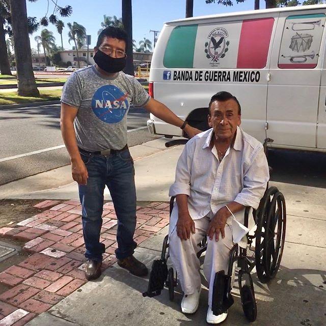 Hombre entregándole a don Joel su silla de ruedas nueva