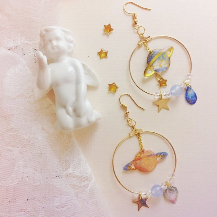 Gold-colored universe-inspired earrings with saturn on them