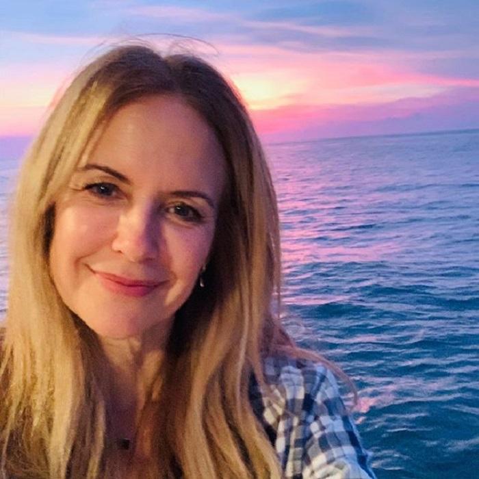 Kelly Preston y detrás de ella el mar y un hermoso atardecer