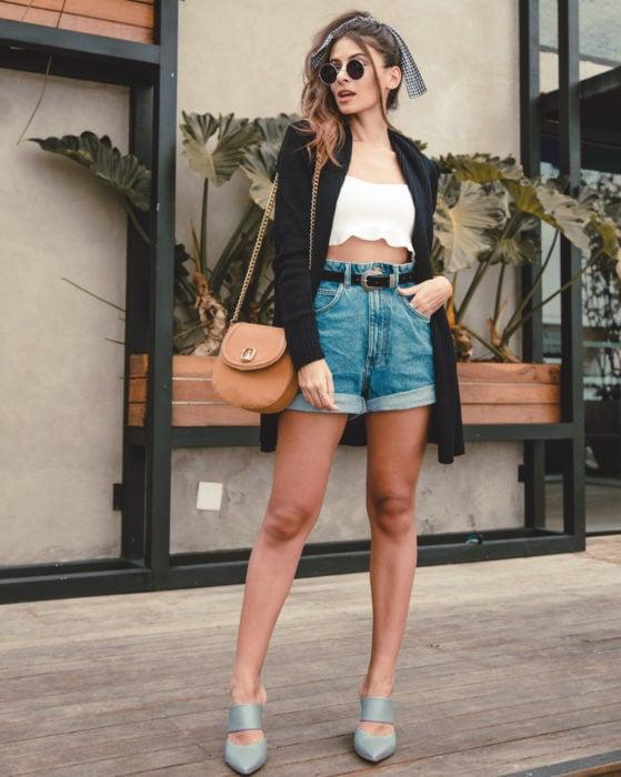 Looks con short vintage; chica con lentes redondos para sol, saco negro, crop top blanco, bolsa beige y sandalias grises