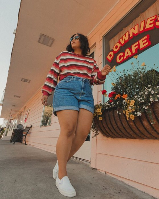 Looks with vintage shorts; plus size woman walking in the street and smiling, short black hair, sunglasses, red, white and brown striped sweatshirt, white tennis shoes