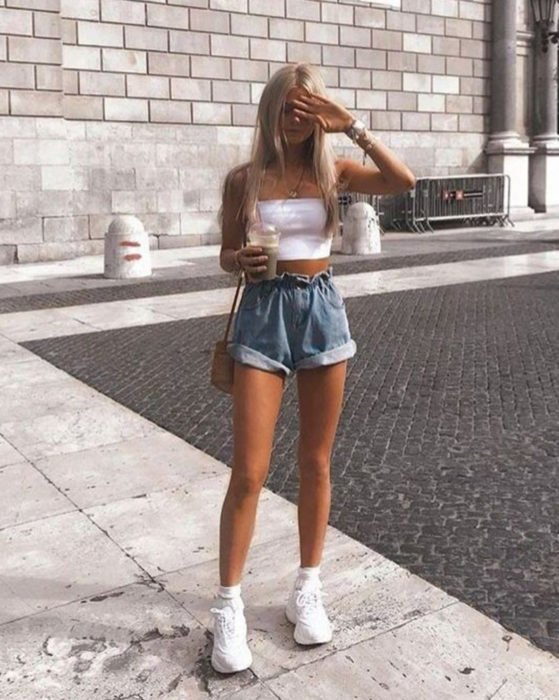 Looks with vintage shorts; girl with long, straight blonde hair, with her hand on her forehead and a platform row tennis shoe, in the street with a frappé