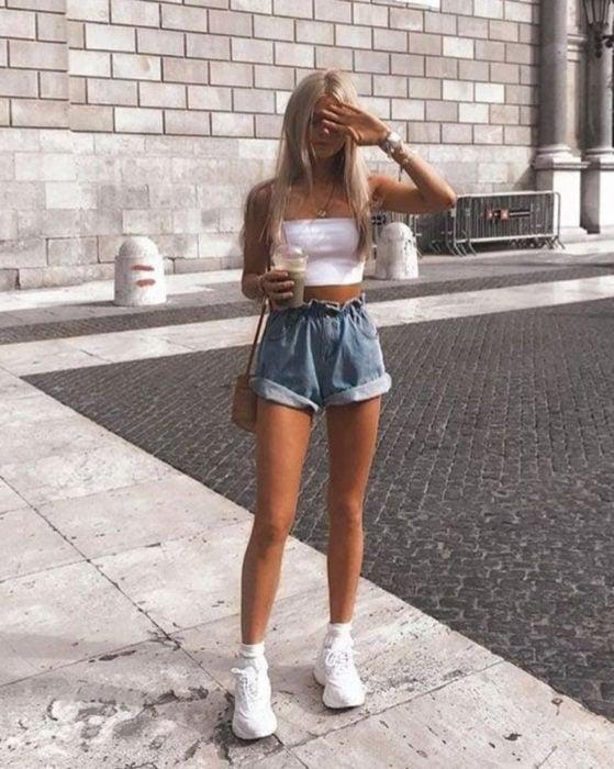 Looks con short vintage; chica de cabello rubio, largo y lacio, con la mano en la frente y tenis fila de plataforma, en la calle con un frappé