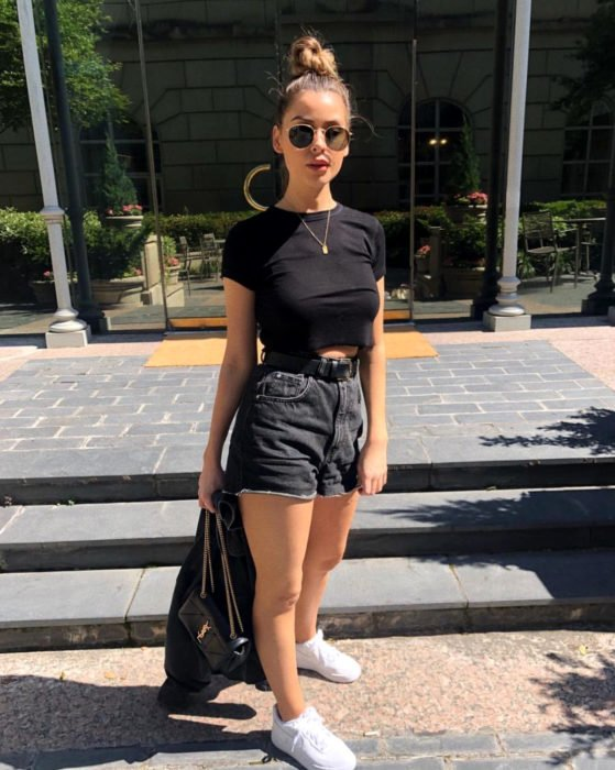 Looks with vintage shorts; girl with high bun hairstyle, black crop top, white tennis shoes, sunglasses