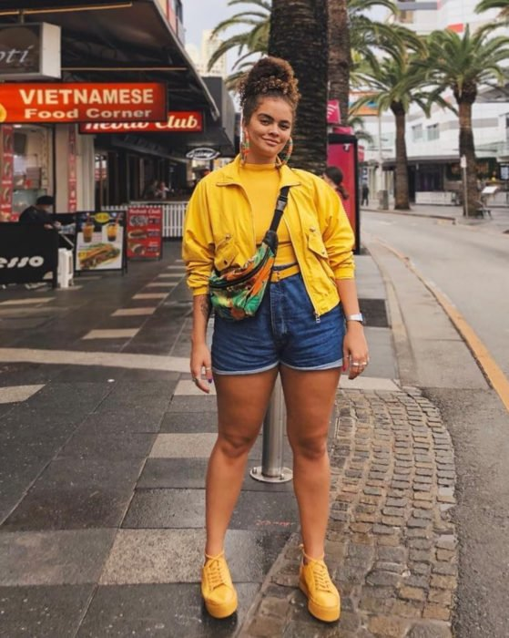 Looks with vintage shorts; brunette girl with Chinese hair combed in a high bun, with tennis shoes, blouse and yellow jacket
