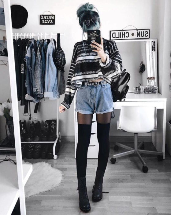 Looks with vintage shorts; girl taking a selfie in front of the mirror, blue hair with black roots, striped sweater, long stockings and Dr. Martens boots