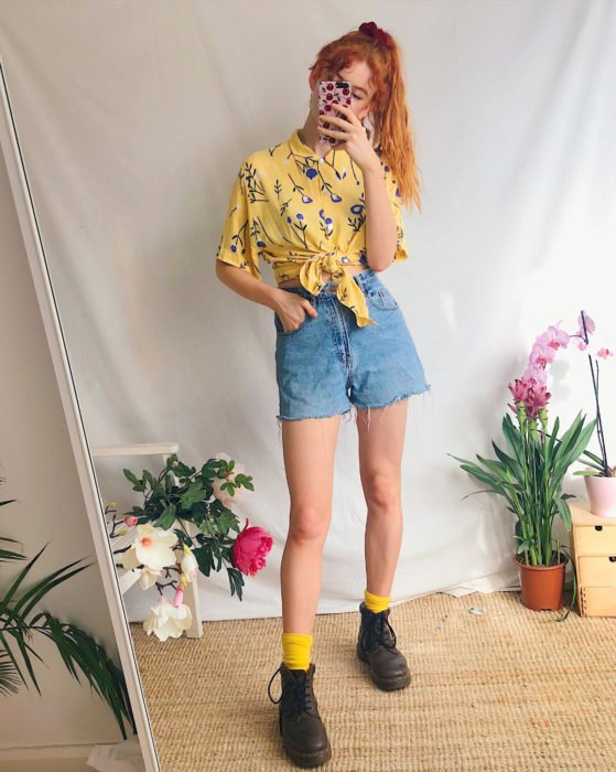 Looks with vintage shorts; red-haired girl taking a selfie in front of the mirror, wearing a yellow floral blouse and Dr. Martens boots