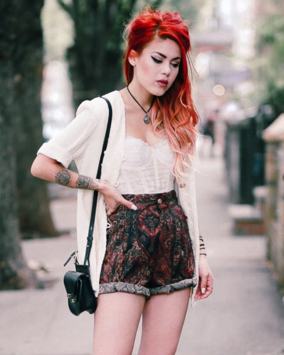 Looks with vintage shorts; red-haired rock girl with flower tattoos on her arms, white stitching and shorts with retro print, knitted sweater and black bag
