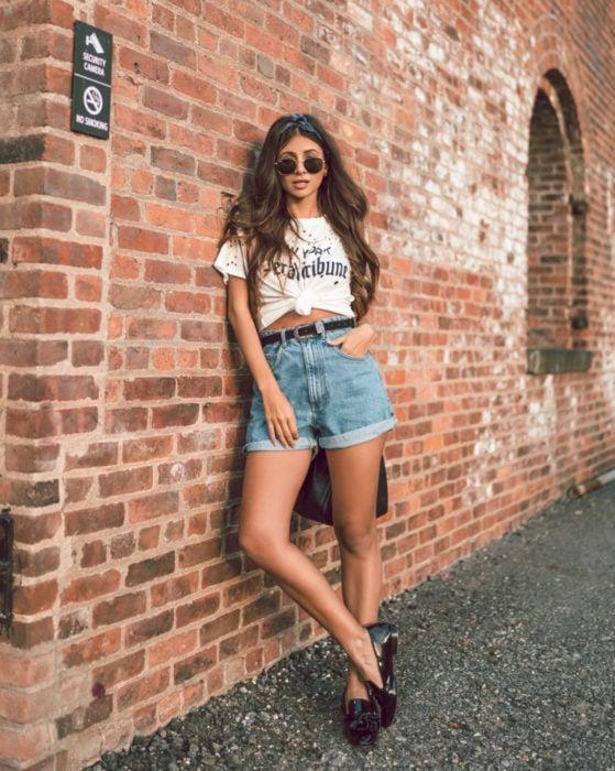 Looks con short vintage;chica recargada en pared de ladrillos, cabello castaño largo y suelto, lentes de sol, blusa blanca y zapatos negros de charol