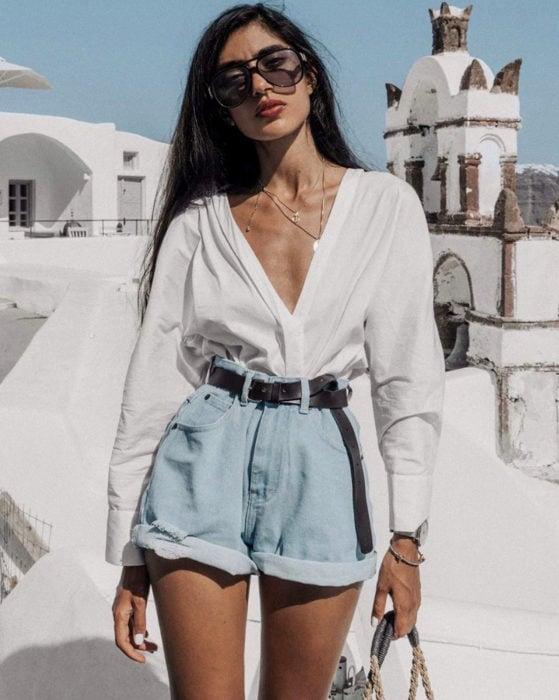 Looks con short vintage; mujer con blusa blanca de vestid, cabello negro lacio y largo, lentes de sol