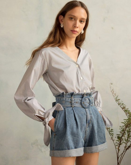Looks with vintage shorts; woman with long straight brown hair in formal blouse