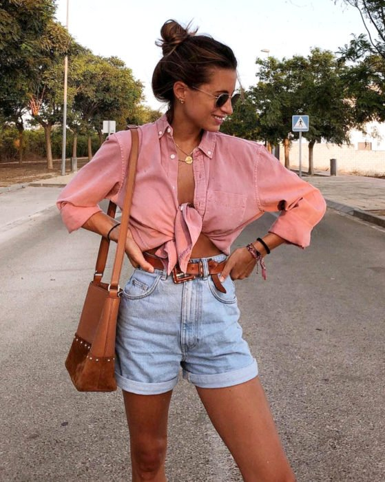 Looks with vintage shorts; woman smiling in the street, with washed red or salmon pink denim blouse and brown bag, high bun hairstyle and sunglasses, hands on hips