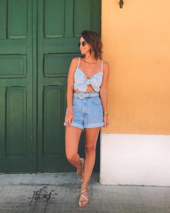 Looks con short vintage; mujer recargada en la pared frente a una puerta antigua verde, cabello corto a los hombros, estilo playero, top rayado con moño, sandalias doradas