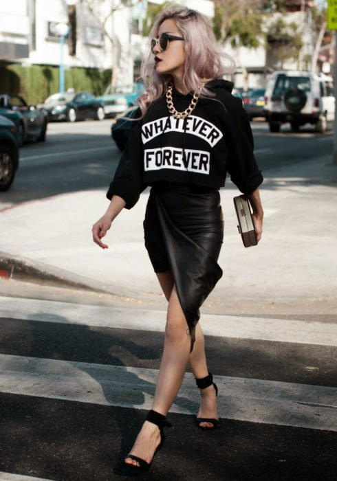 Looks with sweatshirt; woman walking in the street, pink hair, long, wavy, black hoodie, gold chain necklace, black leather skirt, heels