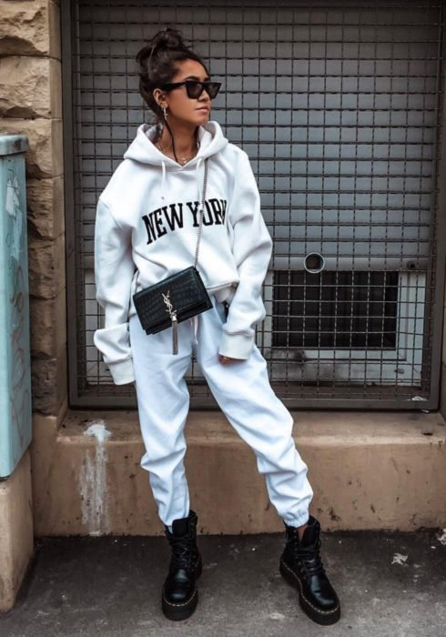 Looks with sweatshirt; woman on the street with high bun hairstyle, modern sunglasses, white hoodie with New York print, pants, black bag, Dr. Martens military boots