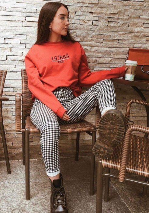 Looks with sweatshirt; woman sitting in restaurant chair, with long, straight, auburn hair, red hoodie, black and white plaid pants and Dr. Martens boots