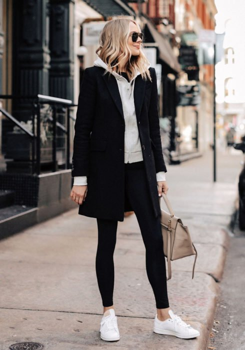 Looks with sweatshirt; woman on the street, blonde, short and wavy hair, dark sunglasses, gray hoodie, medium black coat, leggings, white tennis shoes and beige bag