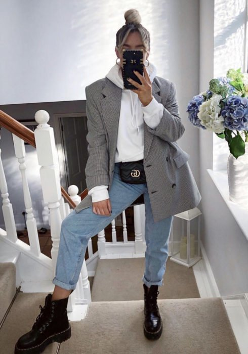 Looks with sweatshirt; woman taking selfie in front of the mirror, platinum blonde hair with high bun hairstyle, white hoodie, gray plaid jacket, blue mom jean pants, fanny pack and black Dr. Martens boots