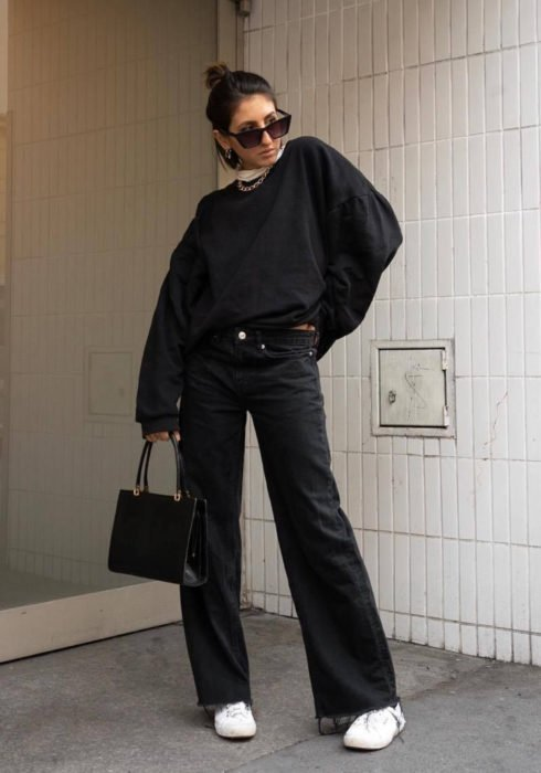 Looks with sweatshirt; short brown hair woman with ponytail hairstyle, oversized sunglasses, oversized black hoodie, flared jeans, white tennis shoes and handbag