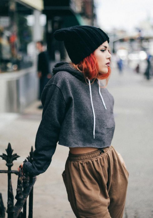 Looks with sweatshirt; Red-haired girl with urban clothing style, dark gray crop top hoodie, cold knit hat, brown pants