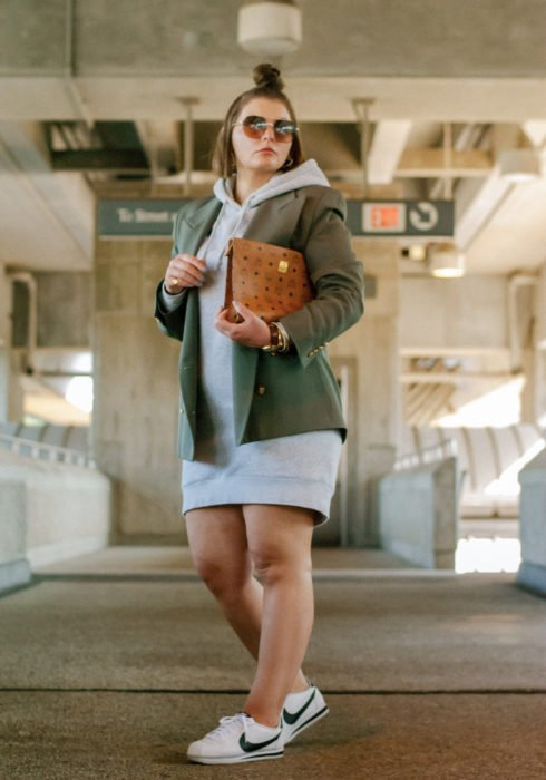 Looks with sweatshirt; plus size girl wearing gray hoddie as dress, with military green jacket, white Nike tennis shoes and brown wallet bag; hairstyle for short hair hairstyle with medium high bun