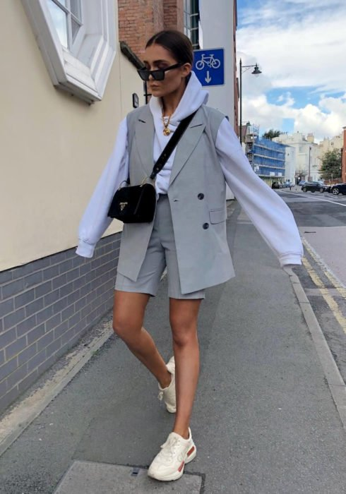 Looks with sweatshirt; woman walking in the street with sunglasses, dressed in sky blue hoodie, gray vest and shorts, beige tennis shoes, black bag