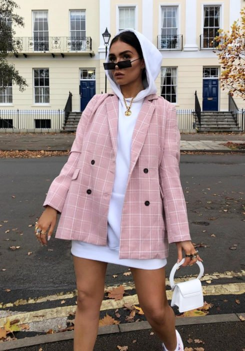 Looks with sweatshirt; woman walking in the street with a white hoodie as a dress, a pink jacket with squares, a small white bag and rectangular sunglasses