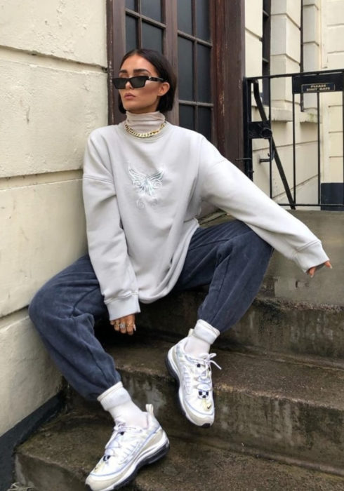 Looks with sweatshirt; woman with sunglasses sitting on stairs, with white gray oversized hoodie, mom jeans and sports sneakers