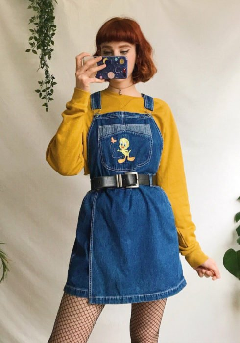 Looks with sweatshirt; girl with short red hair with fringe taking selfie in front of the mirror, canary yellow hoodie, overalls dress with Tweety print, black belt, fishnet stockings