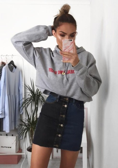 Looks with sweatshirt; woman taking selfie in front of the mirror, high bun hairstyle, gray hoodie, denim skirt, denim