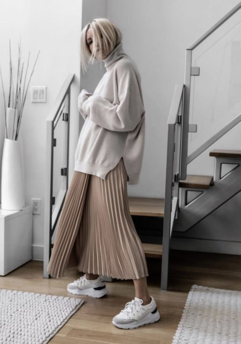 Looks with sweatshirt; woman with platinum blonde hair, gray white hoodie, pleated maxi skirt and sports Skechers sneakers