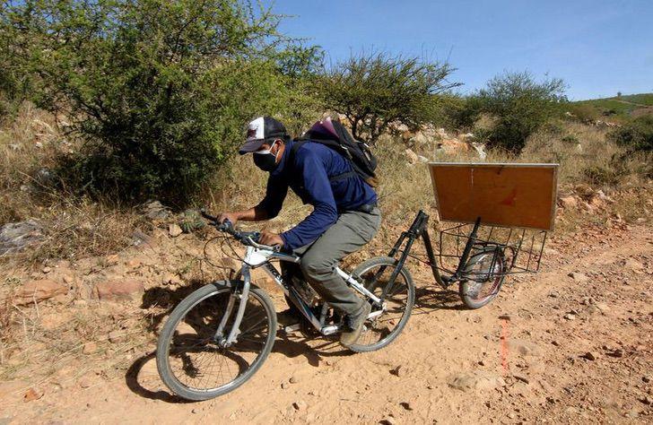 Maestro conduciendo su bicicleta para dar clases en una comunidad indígena