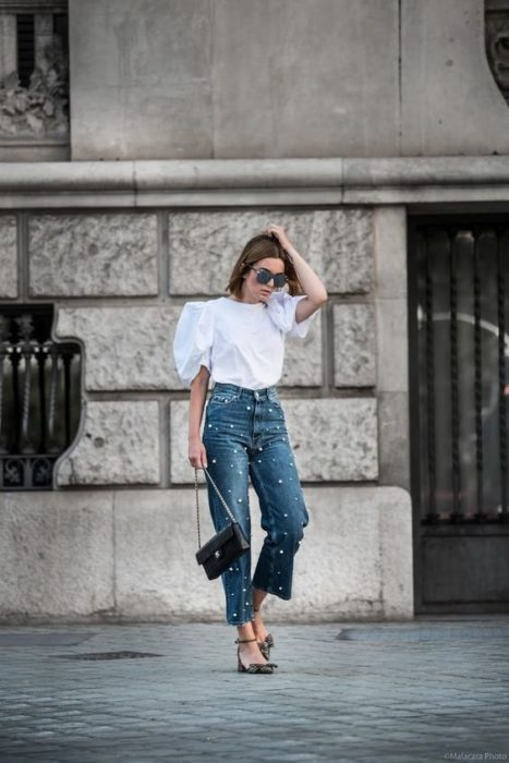 Woman posing in white blouse and jeans with pearl appliqués