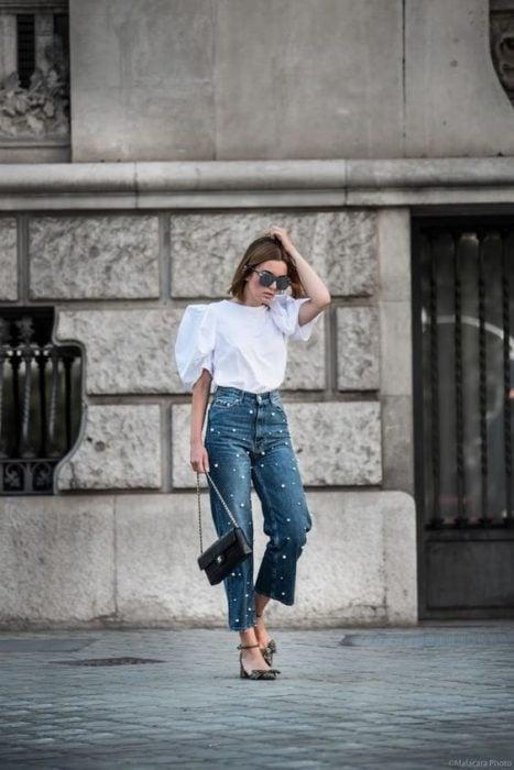 Mujer posando con blusa blanca y jeans con aplicaciones de perlas
