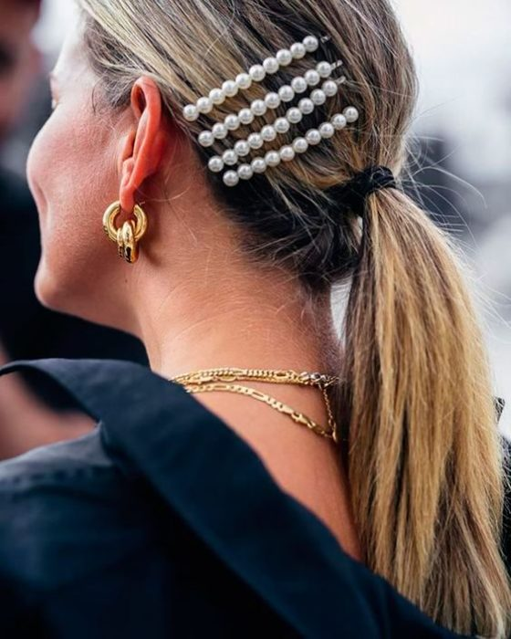 Blonde woman with low ponytail and pearl brooches