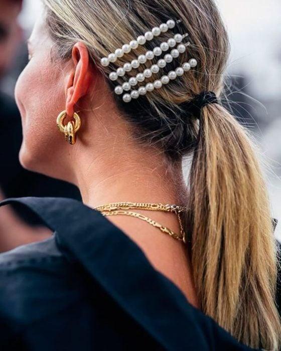 Mujer rubia con coleta baja y broches de perlas