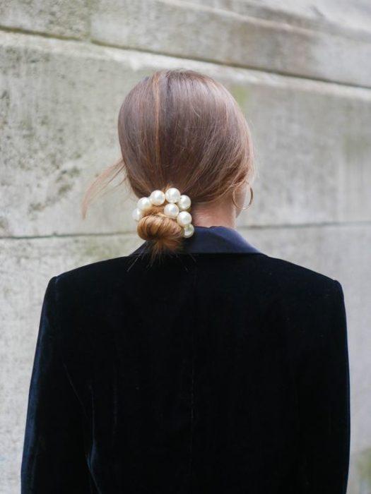 Mujer con chongo bajo y liga con perlas